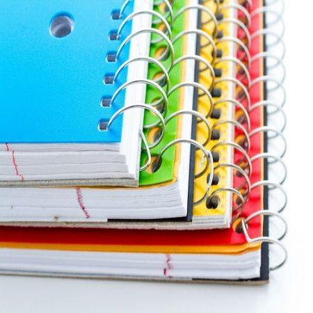 Multicolored spiral notebooks on a white background.